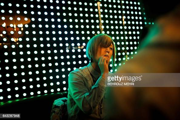 In this picture taken on January 28 a male host smokes as he accompanies a female customer at a host club in the Kabukicho redlight district in Tokyo...