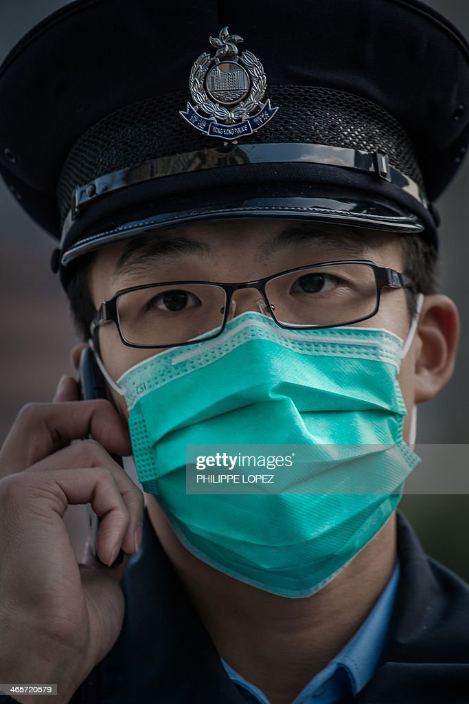 In this picture taken on January 28, 2014, a policeman talks on a mobile phone outside a wholesale market where infected poultry imported from mainland China was discovered in Hong Kong. Hong Kong on January 29, 2014 reported its third death from H7N9 bird flu -- an elderly man who had visited mainland China -- a day after authorities culled 22,000 birds to curb the disease. AFP PHOTO / Philippe Lopez
