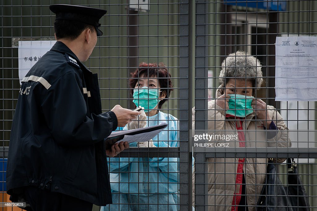 In this picture taken on January 28, 2014, a policeman talks to employees of a wholesale market where infected poultry imported from mainland China was discovered in Hong Kong. Hong Kong on January 29, 2014 reported its third death from H7N9 bird flu -- an elderly man who had visited mainland China -- a day after authorities culled 22,000 birds to curb the disease. AFP PHOTO / Philippe Lopez
