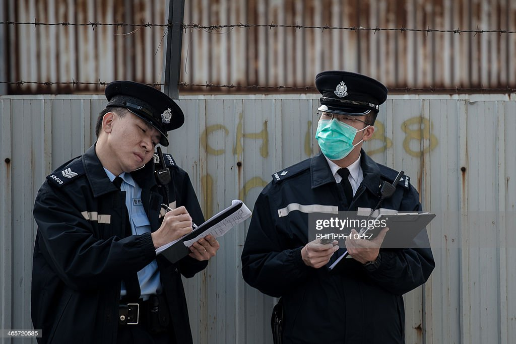 In this picture taken on January 28, 2014, two policemen take notes near a wholesale market where infected poultry imported from mainland China was discovered in Hong Kong. Hong Kong on January 29, 2014 reported its third death from H7N9 bird flu -- an elderly man who had visited mainland China -- a day after authorities culled 22,000 birds to curb the disease. AFP PHOTO / Philippe Lopez