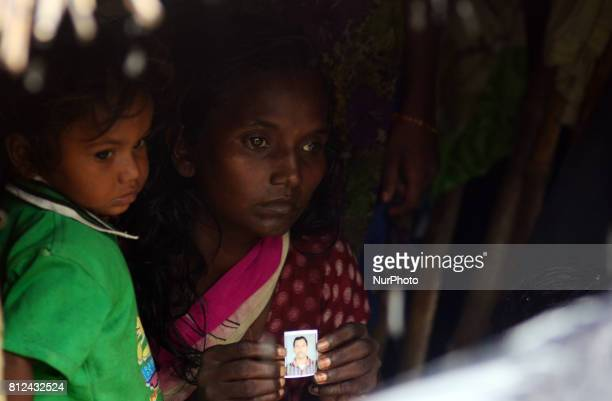 In this picture taken on July 10 Sunita wife of Mohan aged 30 who died of consuming poisonous alcohol shows her husband's photographinside her...