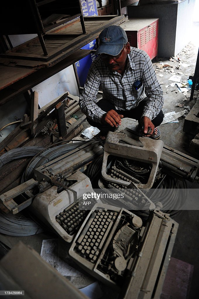 In this picture taken on July 12, 2013, an Indian employee looks at old typewriters laying in a store room at the Targhar telegraph office in Allahabad. Thousands of Indians crammed into telegram offices to send souvenir messages to friends and family in a last-minute rush before the service shuts down. July 14, 2013, is the last day that messages will be accepted by the 162-year-old service, the last major commercial telegram operation. In the days before mobile phones and the Internet, the telegram network was the main form of long-distance communication, with 20 million messages dispatched from India during the subcontinent's bloody partition in 1947. AFP PHOTO/ SANJAY KANOJIA