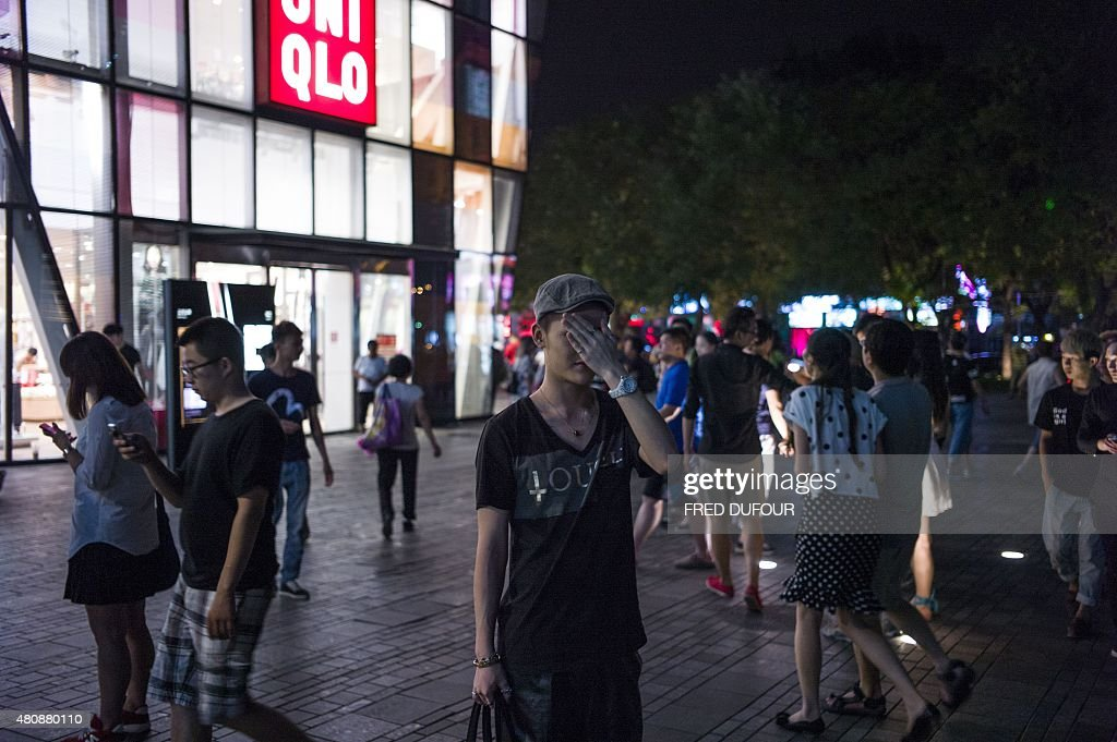 In this picture taken on July 15 people gather in front of a Uniqlo clothes store in Beijing Chinese Communist authorities have said the distribution...