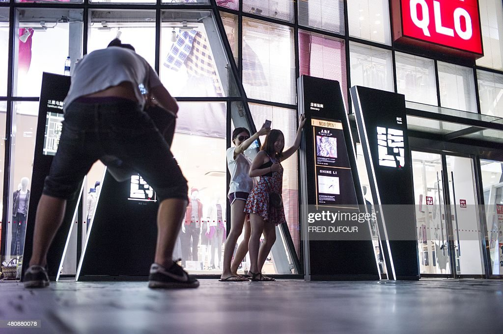 In this picture taken on July 15 people pose in front of a Uniqlo clothes store in Beijing after a sex tape purportedly shot in a fitting room of the...