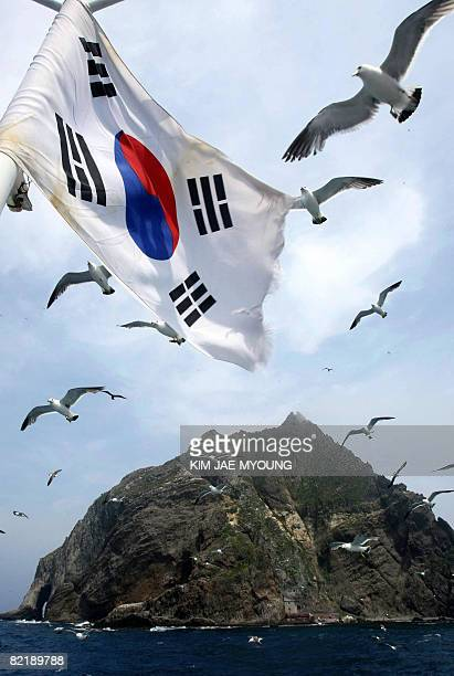 In this picture taken on July 16 A South Korean national flag flutters aboard a tourship during a tour in the Koreancontrolled islands in the Sea of...