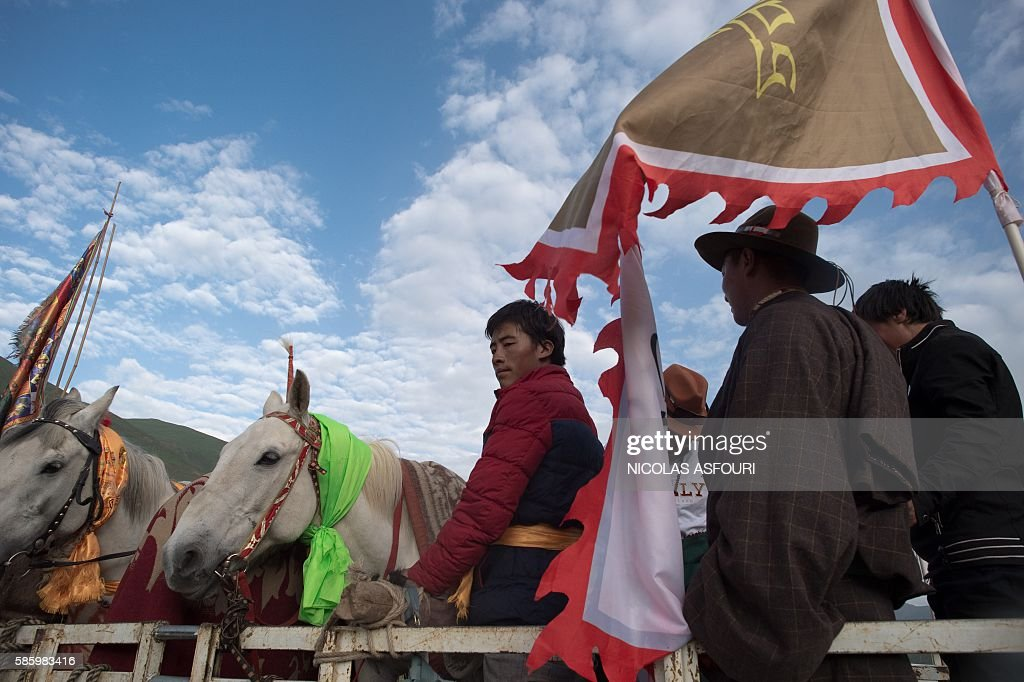 In this picture taken on July 26 2016 Tibetan nomad horsemen stand on the back of a truck with their horses as they travel to participate to a horse...