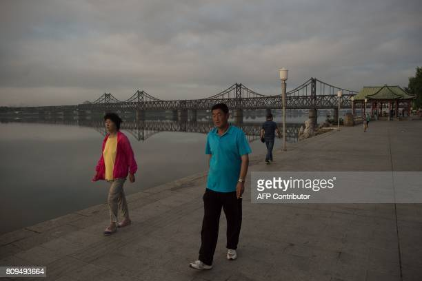 In this picture taken on July 5 2017 people walk as the sun rises over the Friendship bridge on the Yalu River connecting the North Korean town of...