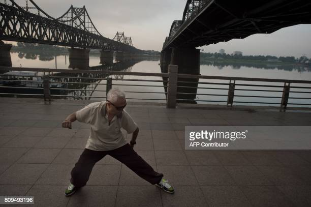 In this picture taken on July 5 2017 the sun rises over the Friendship bridge as a man performs Tai Chi on the Yalu River connecting the North Korean...
