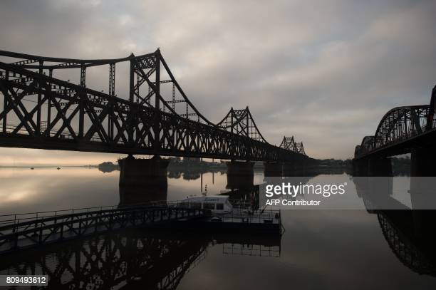 In this picture taken on July 5 2017 the sun rises over the Friendship bridge on the Yalu River connecting the North Korean town of Sinuiju and...
