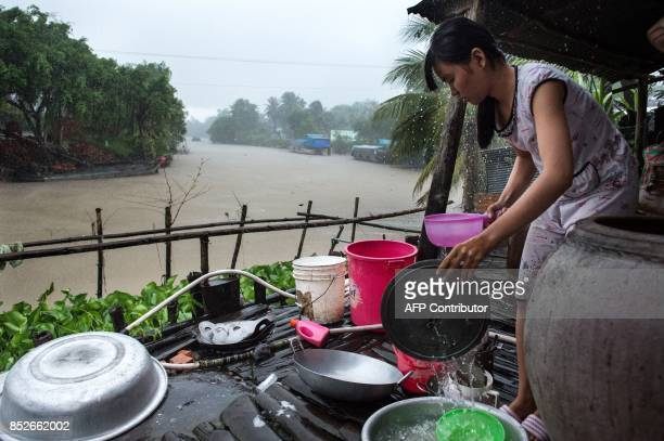 In this picture taken on July 7 16Yearold Dang Thi Bich Thien washes the dishes during a morning monsoon downpour at her home in Thuan Hung Village...