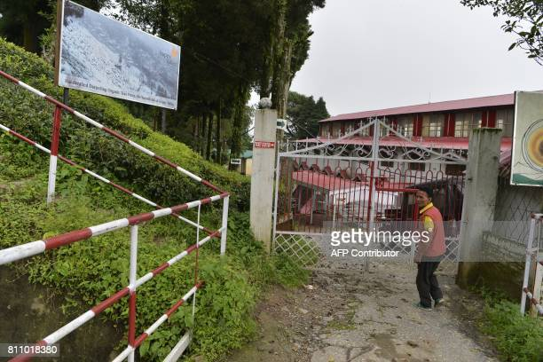 In this picture taken on July 7 2017 shows an Indian caretaker walking near the main entrance of the high altitude Happy Valley Tea garden factory...