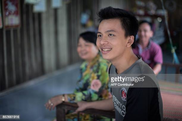 In this picture taken on July 7 26yearold Bui Minh Phi smiles as he sits near his parents at their home in Thuan Hung Village in the Mekong Delta The...