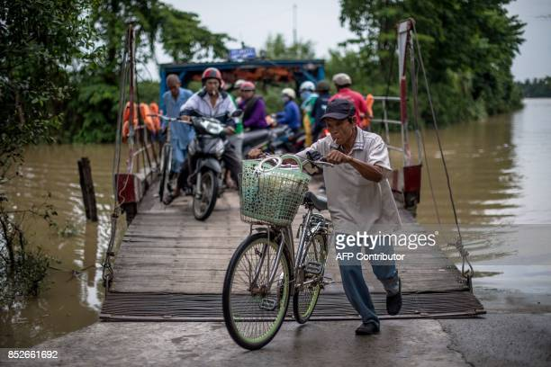In this picture taken on July 7 a commuter pushes his bicycle off a ferry after crossing the Hau river near Thuan Hung Village in the Mekong Delta...