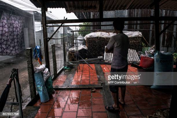 In this picture taken on July 7 a man watches a heavy morning monsoon downpour at his home in Thuan Hung Village in the Mekong Delta The man's family...