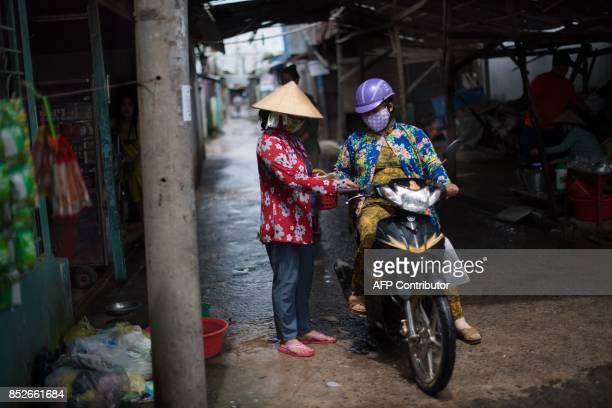 In this picture taken on July 7 a woman on a motorcycle pays for a ferry ride to cross the Hau river near Thuan Hung Village in the Mekong Delta rice...