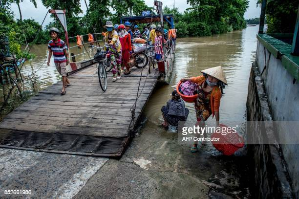In this picture taken on July 7 a woman who had just finished washing clothes by the river walks past a ferry boat at a river crossing near Thuan...