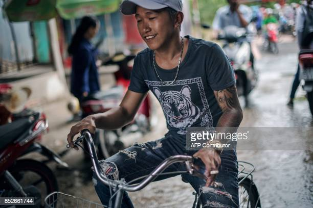 In this picture taken on July 7 a young man rides a bicycle near the entrance of a ferry stop along the Hau river near Thuan Hung Village in the...