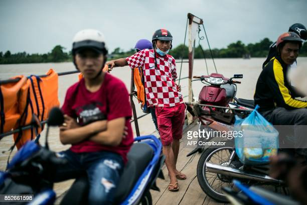 In this picture taken on July 7 commuters ride a ferry across the Hau river near Thuan Hung Village in the Mekong Delta The village is renowned for...