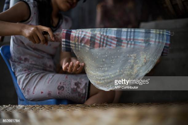 In this picture taken on July 7 Dang Thi Bich Thien rolls rice paper onto a mat for drying at their home in Thuan Hung Village in the Mekong Delta...