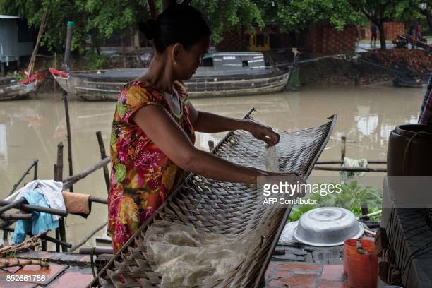 In this picture taken on July 7 Ha Thi Sau collects damaged rice paper from a palm tray at their home in Thuan Hung Village in the Mekong Delta rice...