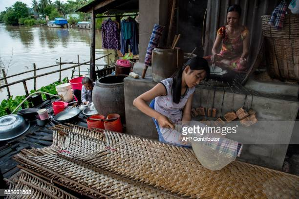 In this picture taken on July 7 Ha Thi Sau pours a rice and sesame mixture onto a hot fire stove as her 16yearold daughter Dang Thi Bich Thien rolls...
