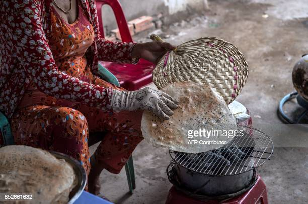 In this picture taken on July 7 Nguyen Thi Hue cooks rice paper over a makeshift charcoal stove at the exit of a ferry crossing near Thuan Hung...