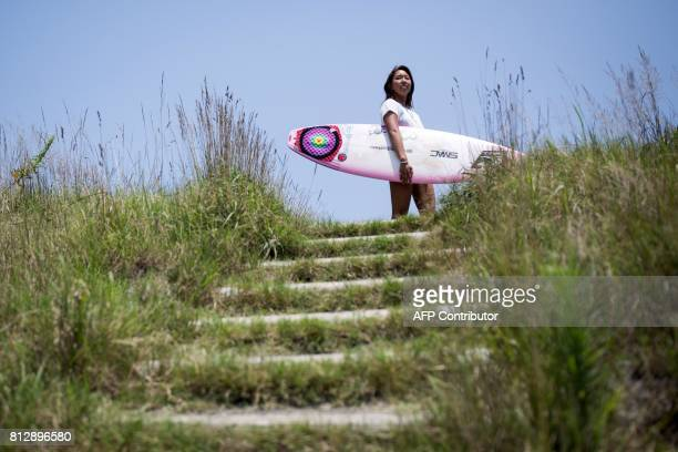 In this picture taken on July 8 Japanese surfer Minori Kawai carries her surfboard before a training session in the town of Ichinomiya Chiba...
