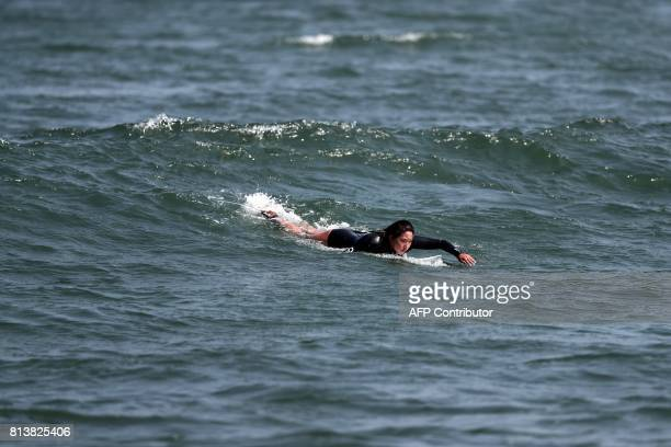 In this picture taken on July 8 Japanese surfer Minori Kawai swims on a surfboard during a training session in the town of Ichinomiya Chiba...