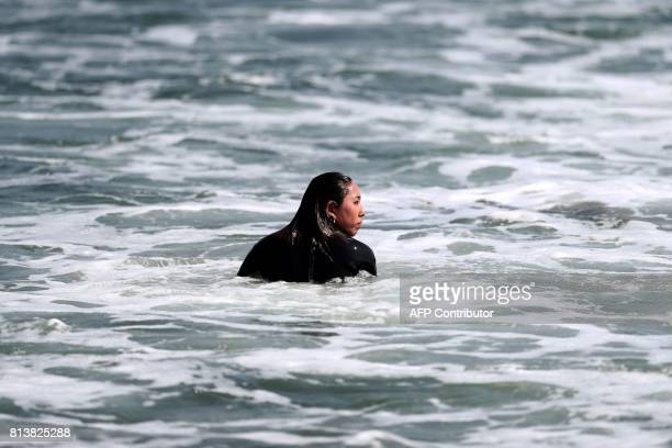 In this picture taken on July 8 Japanese surfer Minori Kawai waits for a wave to surf during a training session in the town of Ichinomiya Chiba...