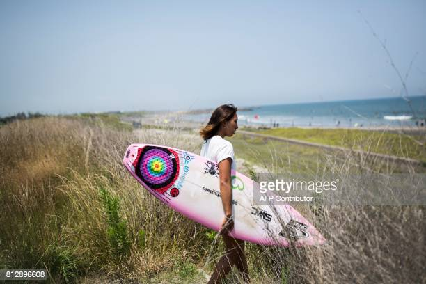 In this picture taken on July 8 Japanese surfer Minori Kawai walks to the beach for a training session in the town of Ichinomiya Chiba prefecture...