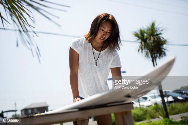 In this picture taken on July 8 Japanese surfer Minori Kawai waxes her surfboard before a training session in the town of Ichinomiya Chiba prefecture...