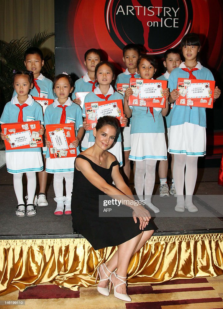 In this picture taken on June 11, 2012 US actress Katie Holmes poses with a group of young Chinese figure skaters as she attends a promotion for the 2012 edition of 'Artistry on Ice' in Beijing. The 'Artistry on Ice' will be performed at the Capital Gymnasium in Beijingon June 12, bringing together many of the world's top figure skaters, including Russia's Evgeni Plushenko, Canada's Kurt Browning, USA's Johnny Weir, South Korea's Yuna Kim, Japan's Shizuka Arakawa and USA's Alissa Czisny, in this year's theme performance entitled 'Red Temptation'. CHINA
