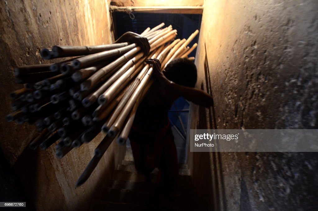In this picture taken on June 16,2017,An Indian worker carries bamboo sticks to dry vermicelli,a traditional sweet dish , ahead of Eid Al Fitr festival , at a factory , in the old streets of Allahabad. Muslims throughout the world are marking the month of Ramadan, the holiest month in the islamic calender.Eid Al -Fitr (feast of breaking the fast) is an important religious festival celebrated by muslims worldwide that marks the end of Ramadan, the islamic holy month of fasting.