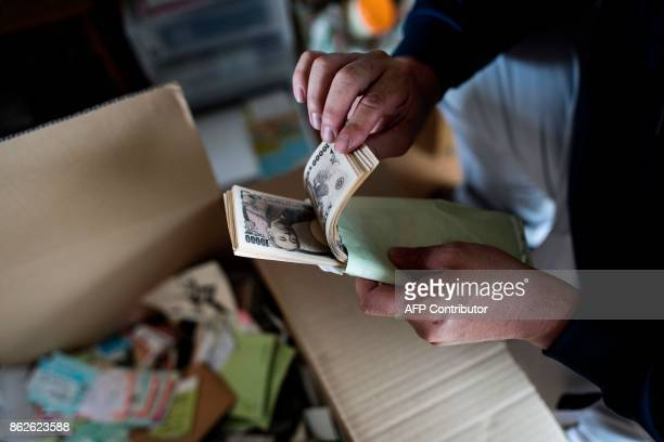 In this picture taken on June 21 a cleaning company worker finds a stack of Japanese yen notes as he cleans up a woman's apartment in Yokohama who...