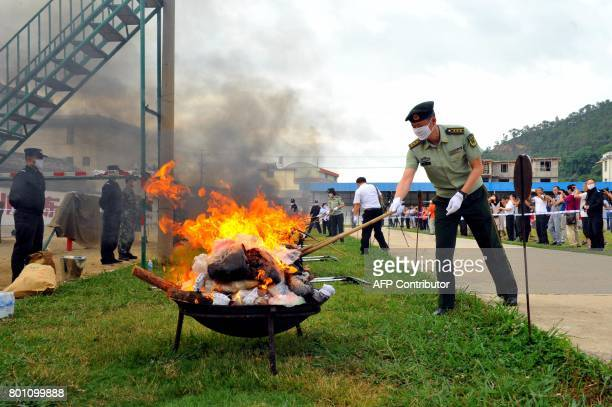In this picture taken on June 25 Chinese army soldiers burn piles of drugs during a destruction ceremony a day ahead of the UN's 'International Day...