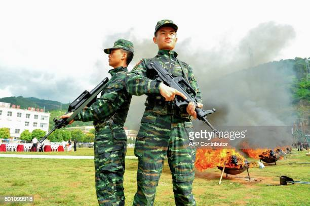 In this picture taken on June 25 Chinese army soldiers stand guard next to burning piles of drugs during a destruction ceremony a day ahead of the...