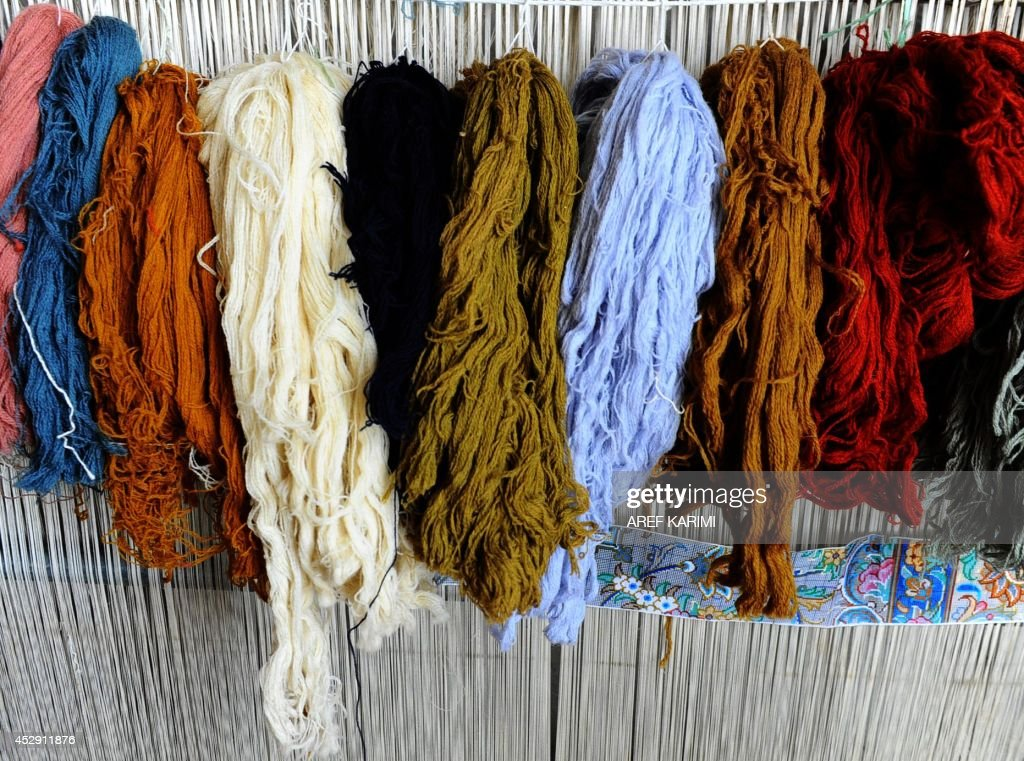 In this picture taken on June 25, 2014, coloured threads to be woven into a carpet hang inside a traditional factory in Afghanistan's province of Herat. The Department of Agriculture in Herat, in cooperation with a non-profit organisation, provided some 5,050 silkworm boxes in the beginning of 2014 to several districts to revive silk production in the region. Some 42,500 women and their families are involved in the project which aims to provide a means of subsistence and potentially lead to international market access for silk producers in the country. Western Afghanistan, once a stop along the Silk Road trade route, has a long tradition in the silk production process dating back thousands of years. Carpets are Afghanistan's best-known export, woven mostly by women and children in the north of the country, a trade which once employed, directly or indirectly, six million people, or a fifth of the country's population, but that figure has dropped sharply. The popular wool and silk Afghan carpets made by different tribes sells from between 150 - 1,000 US dollars. AFP PHOTO/Aref Karimi
