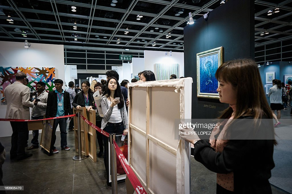 In this picture taken on March 17, 2013 people queue to get their artworks wrapped at the Affordable Art Fair in Hong Kong. The fair which originated in London in 1999 was staged for the first time in Hong Kong featuring art for sale costing from 1,000HKD to HK100,000 HKD (129USD to 12,885USD). AFP PHOTO / Philippe Lopez ---RESTRICTED