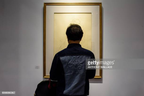 In this picture taken on March 21 a Chinese visitor wearing a jacket with a design that says 'Art Comes First' looks at 'Nude' by JapaneseFrench...