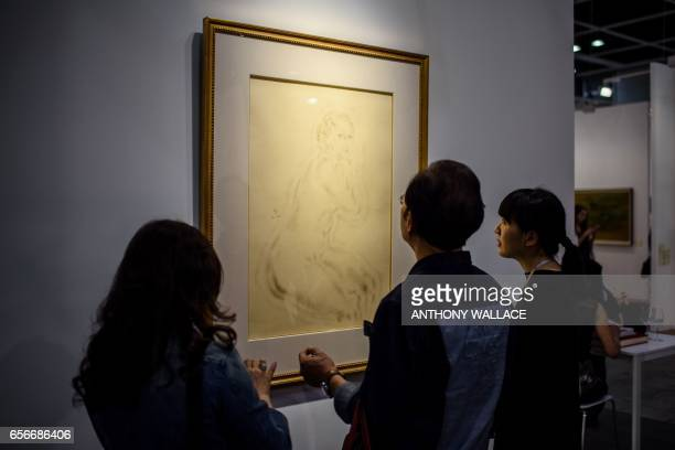 In this picture taken on March 21 Chinese visitors look at 'Nude' by JapaneseFrench painter and printmaker Tsuguharu Foujita at Art Basel in Hong...