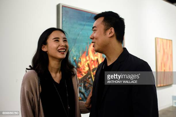 In this picture taken on March 22 Chinese investment banker Huang Xiaoshuai and his wife Wei Mengyuan share a light moment as they stand in front of...