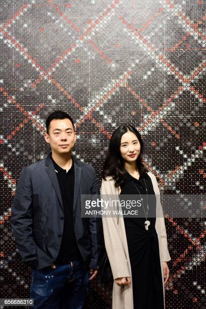 In this picture taken on March 22 Chinese investment banker Huang Xiaoshuai and his wife Wei Mengyuan pose in front of their newly acquired painting...