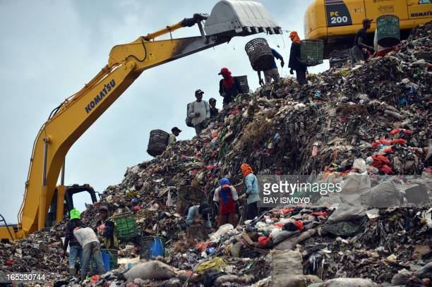 In this picture taken on March 30 2013 people search for material to recycle at the biggest Indonesian capital Jakarta's garbage dump at Bantar...