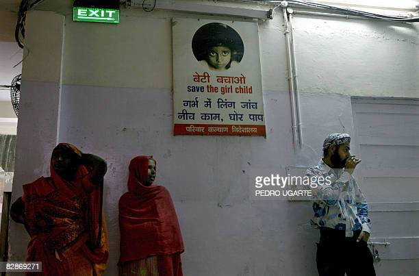 In this picture taken on March 6 Indian visitors stand next to a poster which reads 'save the girl child finding out the gender of a foetus is a sin'...