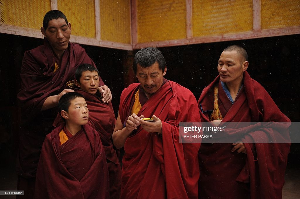 In this picture taken on March 9, 2012, a 2.14 metre Mongolian monk (Top-L) looks at a Tibetan monks iphone pictures with his fellow Tibetan monks after taking part in a ceremony at Lajia Monestry in China's northwest Qinghai province. Overseas rights groups say three Tibetans have self-immolated in China in recent days as Beijing tightens security ahead of the sensitive anniversary of deadly 2008 riots. AFP PHOTO/Peter PARKS