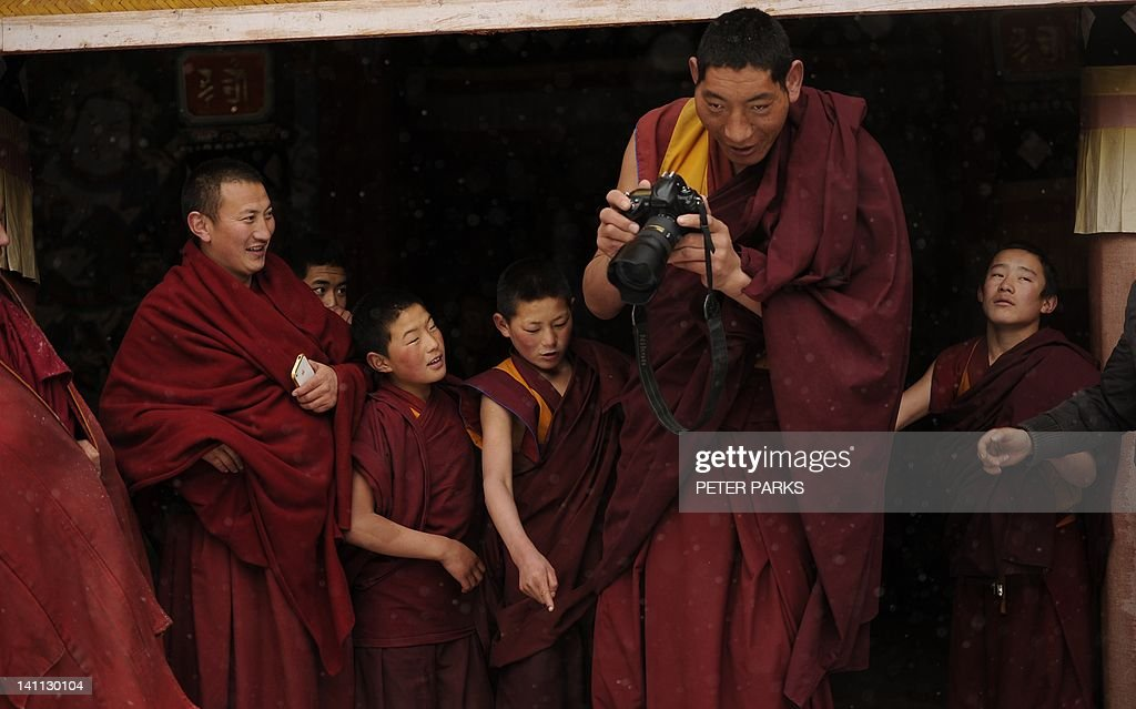 In this picture taken on March 9, 2012, a 2.14 metre Mongolian monk (R) tries a photographer's camera after taking part in a ceremony with his fellow Tibetan monks at Lajia Monestry in China's northwest Qinghai province. Overseas rights groups say three Tibetans have self-immolated in China in recent days as Beijing tightens security ahead of the sensitive anniversary of deadly 2008 riots. AFP PHOTO/Peter PARKS