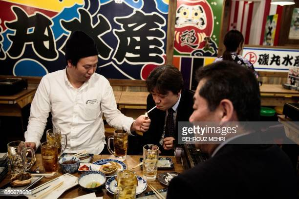 In this picture taken on March 9 a man lights a cigarette for his friend during lunch in a restaurant in the Yurakuchu neighbourhood of Tokyo Japan...