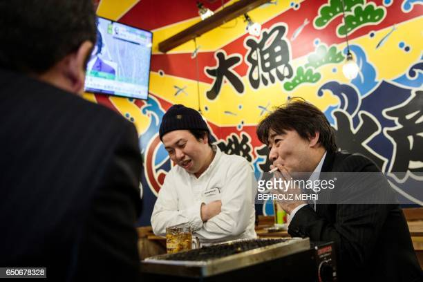 In this picture taken on March 9 a man smokes a cigarette during lunch inside a restaurant in the Yurakuchu neighbourhood of Tokyo Japan is moving to...
