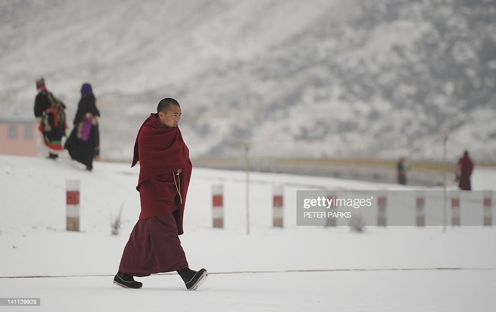 In this picture taken on March 9, 2012, A Tibetan monk walks through Lajia Monestry in China's northwest Qinghai province. Overseas rights groups say three Tibetans have self-immolated in China in recent days as Beijing tightens security ahead of the sensitive anniversary of deadly 2008 riots. AFP PHOTO/Peter PARKS