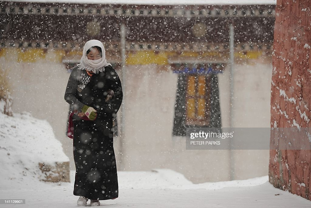 In this picture taken on March 9, 2012, a Tibetan pilgrim walks through Lajia Monestry in China's northwest Qinghai province. Overseas rights groups say three Tibetans have self-immolated in China in recent days as Beijing tightens security ahead of the sensitive anniversary of deadly 2008 riots. AFP PHOTO/Peter PARKS